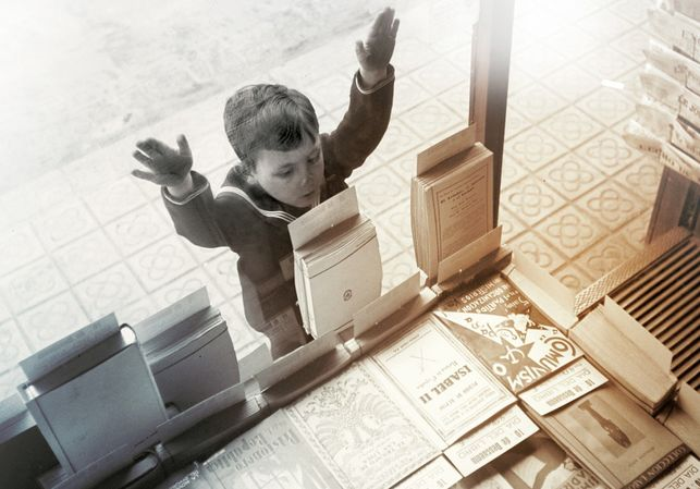 Jongetje staat voor etalage boekwinkel